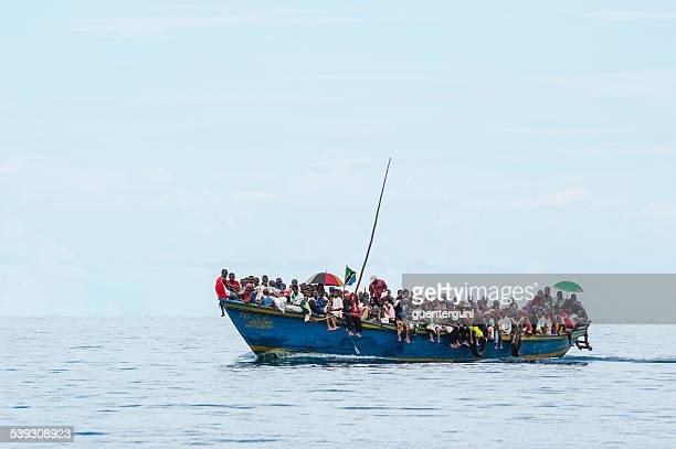 crowded refugee boat on lake tanganyika - nautical vessel stock photos and pictures