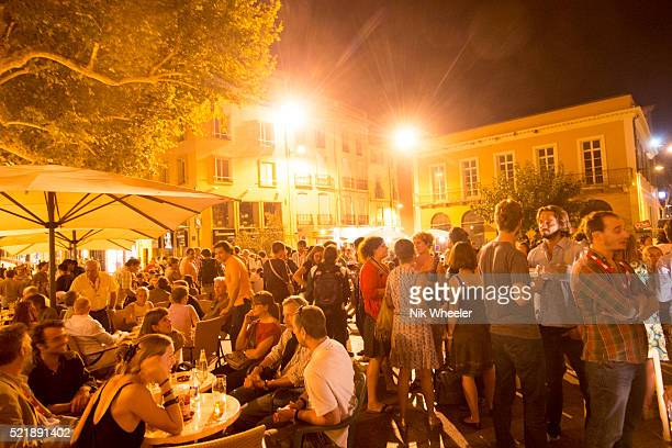 Crowded sidewalk cafe at night in Perpignan, Roussillon, France