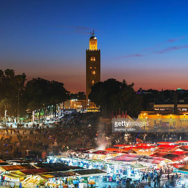 crowded square of marrakech, illuminated at dusk - djemma el fna square stock photos and pictures