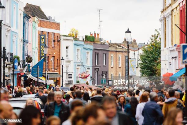 crowded street at portobello road market in notting hill, london, uk - hauptstraße stock-fotos und bilder