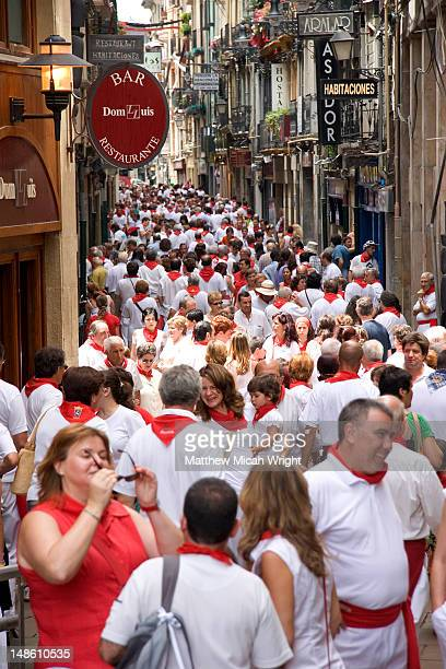 Crowded street of people wearing red and white during San Fermin festival.