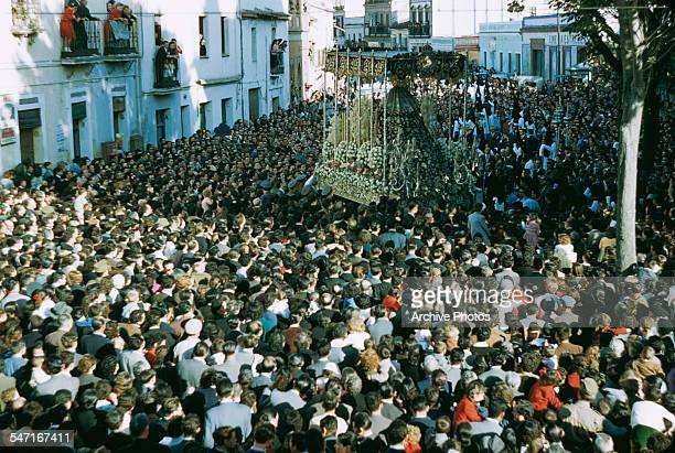 A crowded street procession probably in Spain circa 1960