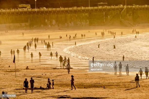 crowded summer beach at sunset - heat haze stock pictures, royalty-free photos & images