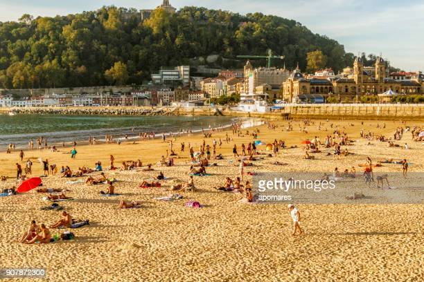 crowded summer beach at sunset - san sebastian spain stock pictures, royalty-free photos & images