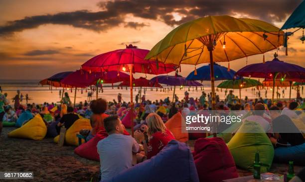 crowded tourists relaxing on the beach at dusk in bali, indonesia - indonesia stock pictures, royalty-free photos & images