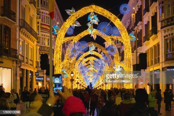 Crowds admiring Christmas street lights display in Calle Larios, the main street of Malaga, Costa del Sol, Malaga Province, southern Spain.