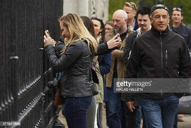Crowds are pictured outside Buckingham Palace in central London on May 2 as they queue to take pictures of an easel announcing that Catherine Duchess...
