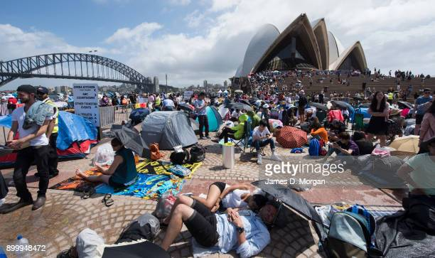 Crowds around the Sydney opera House forecourt start camping out hours before the midnight fireworks on New Year's Eve on December 31 2017 in Sydney...
