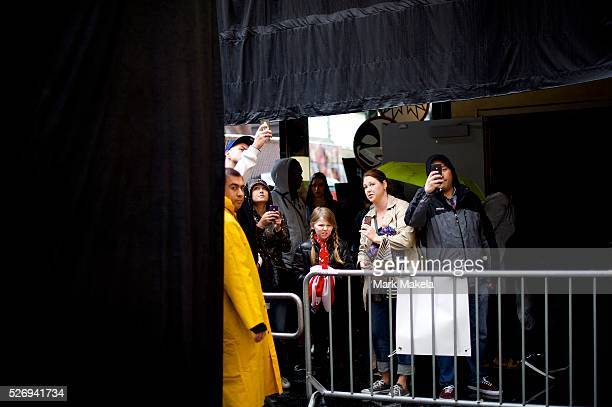 Crowds assemble beside a security barrier to glimpse at Oscar statues arranged on the red carpet the day before the 86th Academy Awards that are...