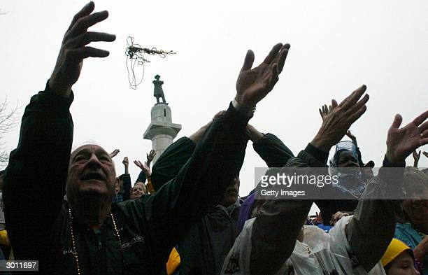 Crowds at a Mardi Gras carnival extend their hands as they try to catch beads in front of Lee Circle February 24 2004 in New Orleans Louisiana Fat...