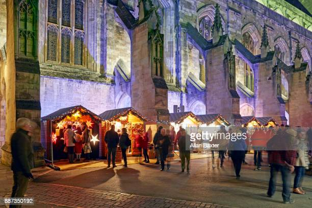 crowds at the christmas market outside winchester cathedral - winchester hampshire stock photos and pictures