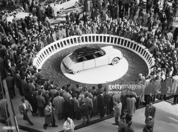 Crowds at the Paris Motor Show in the Grand Palais surround a Citroen DS19 on display