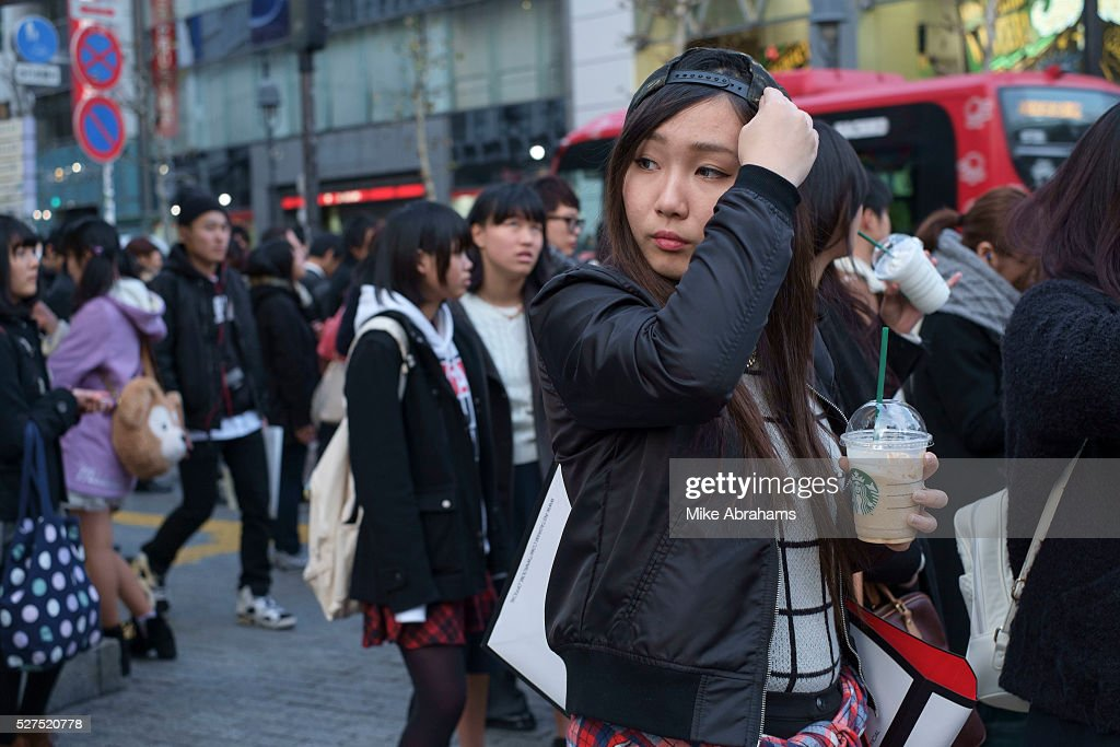 Japan - Tokyo -Young woman with cup of Starbucks coffee in the crowds at the Sibuya crossing : ニュース写真
