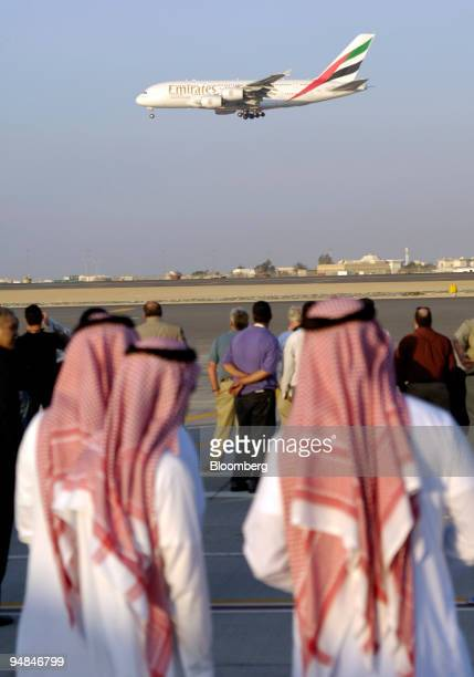 Crowds attending the fourth day of the Dubai Air Show watch an Emirates Airlines Airbus A380 demonstration flight in Dubai United Arab Emirates...