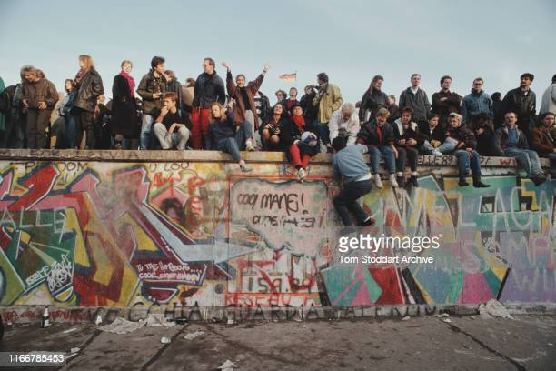 Crowds celebrate on top of the Berlin Wall after the border between East and West Berlin was opened, November 1989. The border was opened on the...