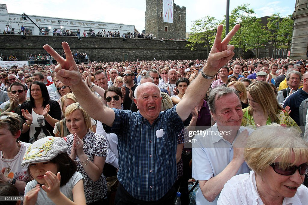 Crowds celebrate the findings of the long-awaited Saville Inquiry report into Bloody Sunday, outside the Guildhall in Londonderry on June 15, 2010. Publication of the report was greeted with cheers in Londonderry, Northern Ireland's second city, where relatives of those who died joined thousands waiting to see the contents of the 5,000-page report. The killings, when British soldiers opened fire on a civil rights march in Londonderry, was one of the most controversial in Northern Ireland's history, and there had been fears the report could re-open wounds. AFP PHOTO / POOL / Paul Faith