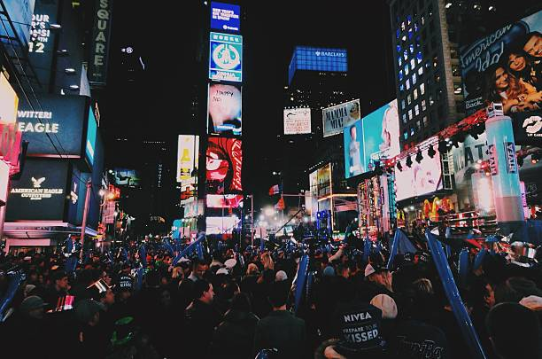 crowds celebrating new year on times square - times square new years eve stock pictures, royalty-free photos & images