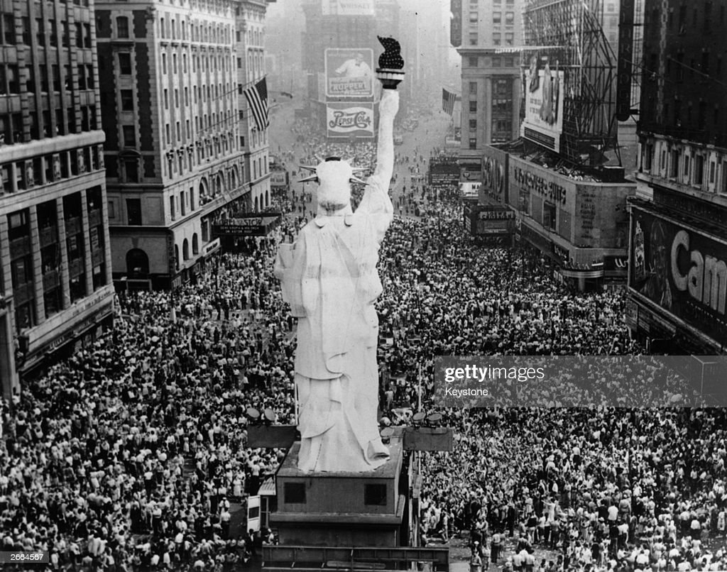Crowds cheering on Great White Way, New York City, as President Truman announces Japan's surrender at the end of World War II. A scaled-down version of the Statue of Liberty is in the foreground.