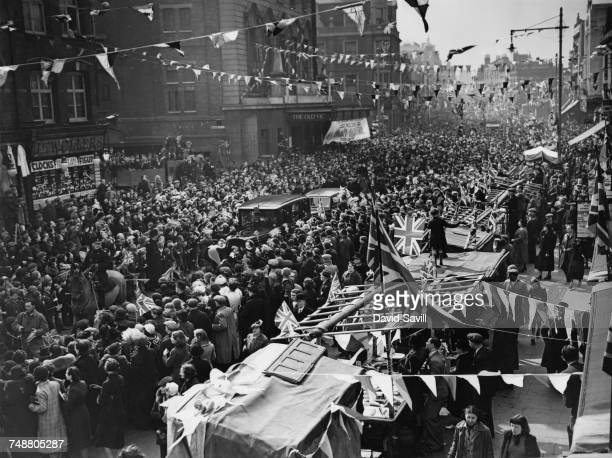 Crowds cheering Queen Mary and her daughter Mary Princess Royal Countess of Harewood as their car makes its way down The Cut in Lambeth London 21st...