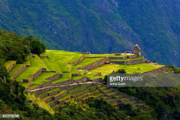 crowds circulate around casa del guardián de la roca funeraria (house of the guardian to the funerary rock) overlooking machu picchu, seen from path to sun gate - inca stock pictures, royalty-free photos & images
