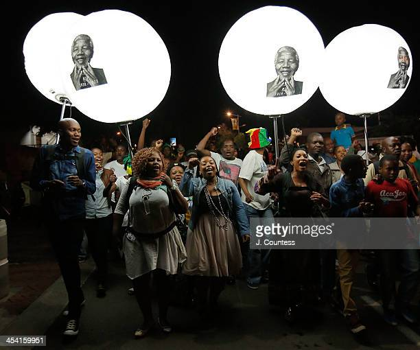 Crowds dance and march on Vilakazi Street in front of the former home of Nelson Mandela on December 7 2013 in Soweto South Africa Mandela also known...