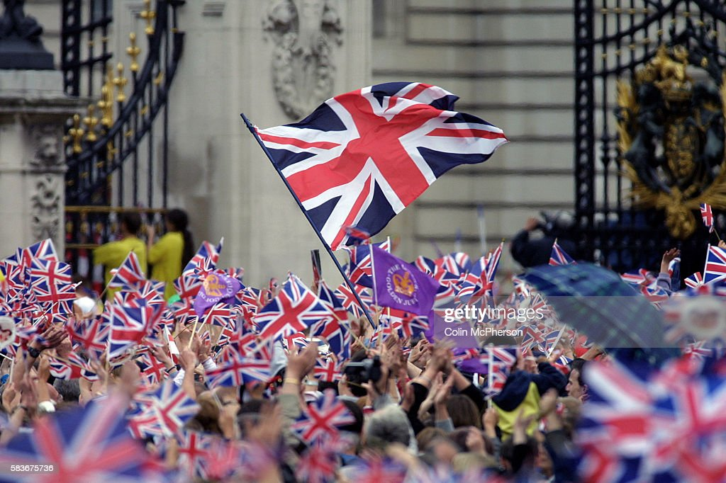 Crowds enthusiastically waving Union flags outside Buckingham Palace as Queen Elizabeth II appears on the balcony of Buckingham Palace at the end of celebrations to mark her Golden Jubilee. Celebrations took place across the United Kingdom with the centrepiece a parade and fireworks at Buckingham Palace, the Queen's London residency. Queen Elizabeth ascended to the British throne in 1952 upon the death of her father, King George VI.