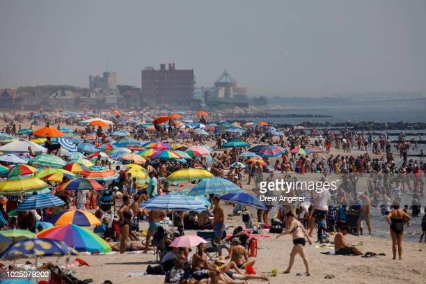 Crowds fill the beach on a hot afternoon at Coney Island, August 29, 2018 in the Brooklyn borough of New York City. The New York City area is under a...