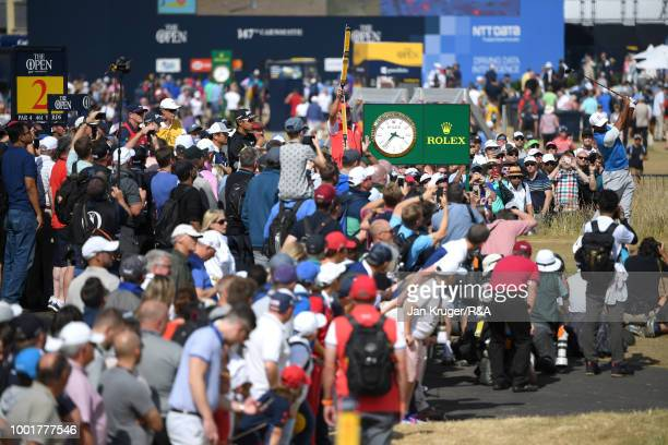 Crowds follow Tiger Woods of the United States as he tees off at the 2nd hole during round one of the 147th Open Championship at Carnoustie Golf Club...