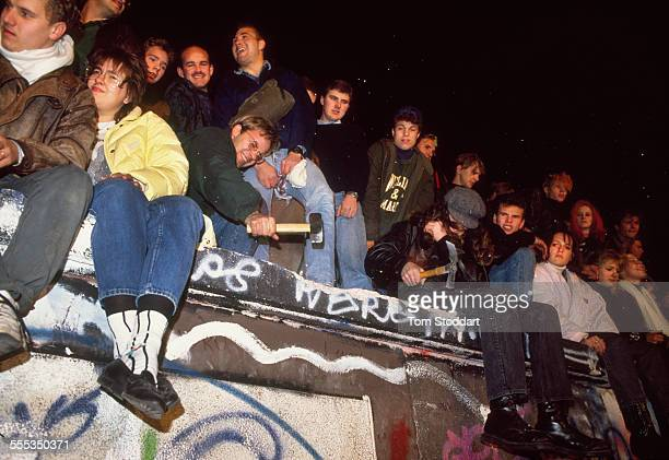Crowds gather and chip away at the wall by Check Point Charlie on the night of November 9 when East Berliners were allowed to cross into the West for...