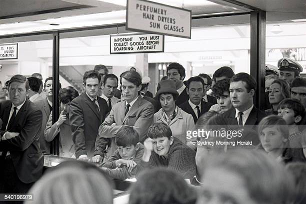 Crowds gather around a television set at a duty free shop at Mascot Airport in Sydney to watch the broadcast of American astronaut Neil Armstrong...