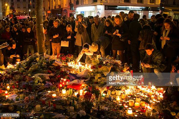 Crowds gather as candles are lit near the Bataclan theatre as France observes three days of national mourning on November 15, 2015 in Paris, France....