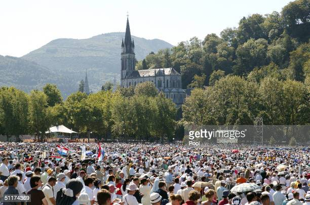Crowds gather as Pope John Paul II celebrates an openair mass on August 15 2004 in Lourdes France The Pope is in Lourdes for a twoday pilgrimage at...