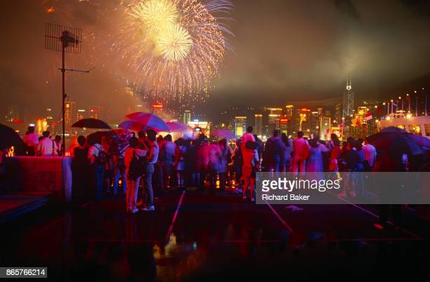 Crowds gather at the stroke of midnight beneath umbrellas to witness the transfer of sovereignty of Hong Kong from the United Kingdom to the Peoples...