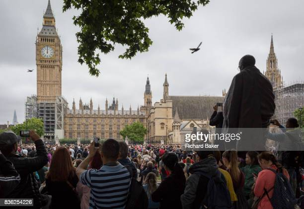 Crowds gather by the statue of Mahatma Gandhi in Parliament Square to hear the last chimes of Big Ben the giant bell in Elizabeth Tower that rings...