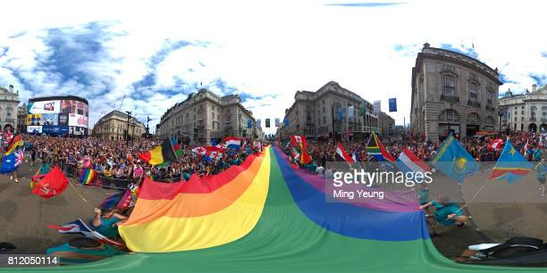Crowds gather in Piccadilly Circus to watch the Pride parade as a rainbow flag goes past on July 8 2017 in London England