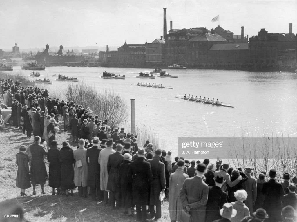 Crowds gather on the banks of the Thames at Mortlake to watch the the finish of the University boat race between Oxford and Cambridge, 24th March 1937.