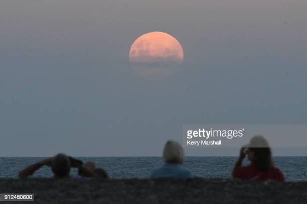 Crowds gather on the Marine Parade Beach to watch the moon rise on January 31 2018 in Napier New Zealand A Super Blue Blood Moon is the result of...