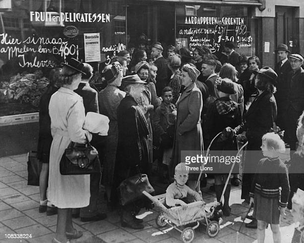 Crowds gather outside a greengrocers in Amsterdam to shop for their weekly supply of food Netherlands circa 1940