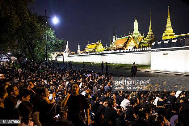 Crowds gather outside of the Grand Palace where King Bhumibol's body was taken after the funeral procession on the evening of October 14 2016 in...