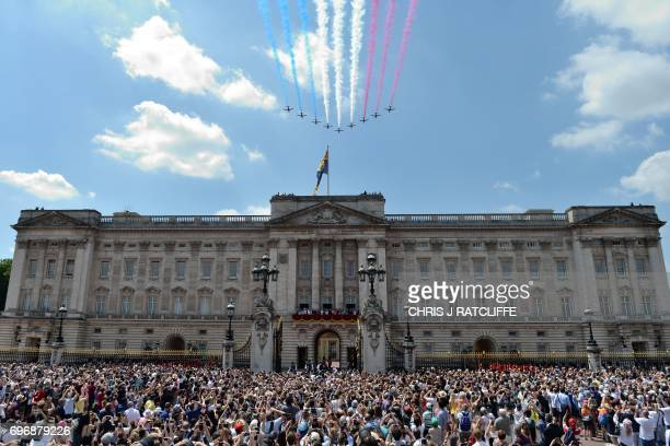 Crowds gather outside the gates as members of the Royal Family stand on the balcony of Buckingham Palace to watch a flypast of aircraft by the Royal...