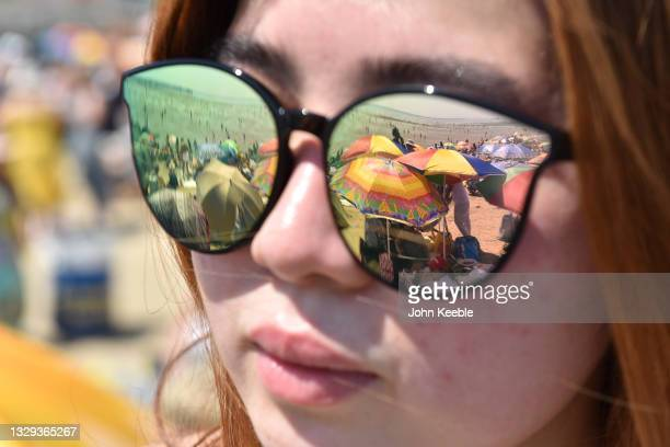 Crowds gather to enjoy the warm sunny weather seen in the reflection of a woman's sunglasses on Jubilee beach on July 18, 2021 in Southend-on-Sea,...