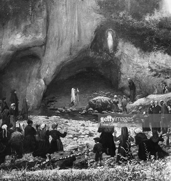 Crowds gather to watch 14yearold MarieBernarde Soubirous a poor French girl experience one of her visions of the Virgin Mary in the grotto of...