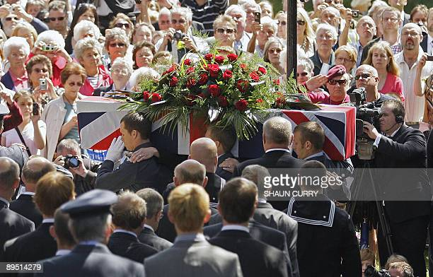 Crowds gather to watch as a coffin bearing the body of Henry Allingham arrives at St Nicholas Church in Brighton, in southern England, on July 30 for...