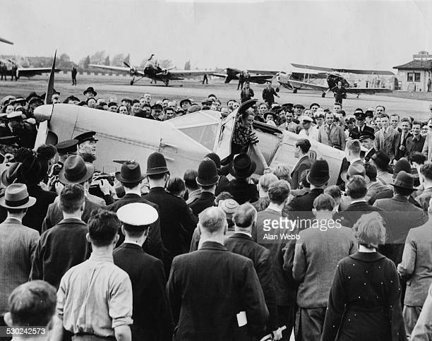 Crowds gather to watch aviator Amy Mollison step out of an airplane to meet her husband Croydon London May 15th 1936