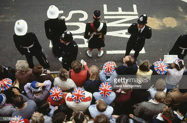 Crowds gather to watch the wedding procession of Prince Charles and Lady Diana Spencer, London, 29th July 1981.