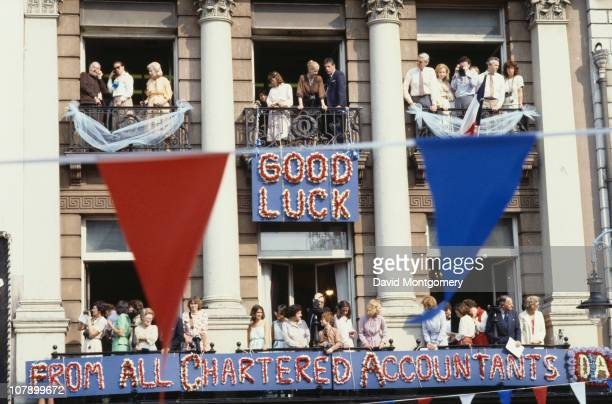 Crowds gather to watch the wedding procession of Prince Charles and Lady Diana Spencer London 29th July 1981 A sign on a building reads 'Good Luck...