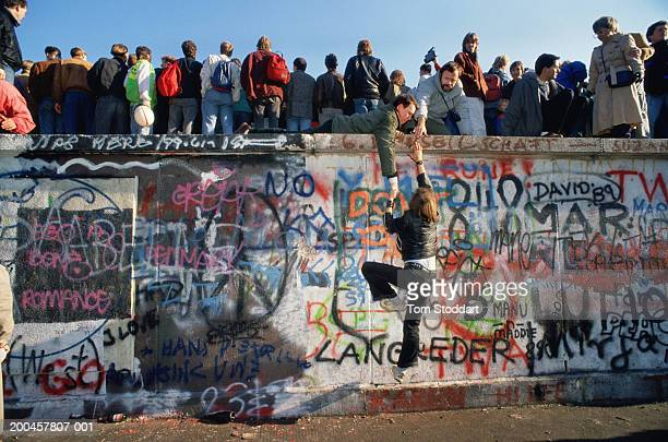 Crowds gathering on Berlin Wall They are on a section of the wall near the Brandenburg Gate – a high profile location where, for cosmetic reasons,...