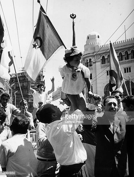 Crowds in Algiers celebrating their country's Independence Day in the city centre A little girl dressed in the Algerian national colours and emblems...