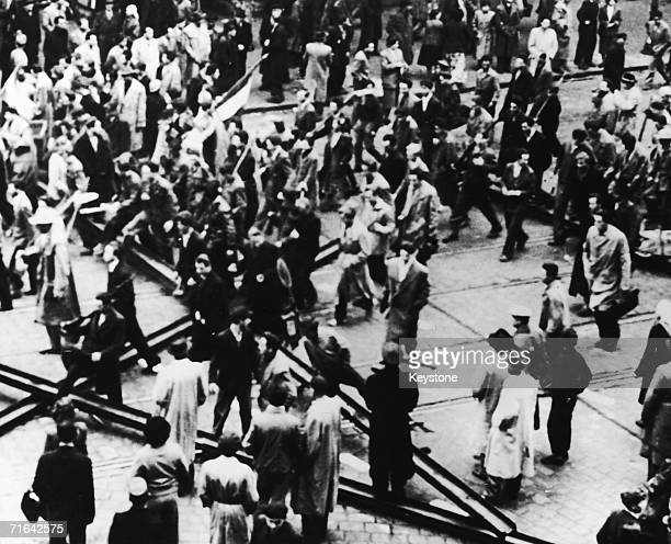 Crowds in Budapest walking over tramlines which have been torn up and used as barricades during the Hungarian Uprising 27th October 1956