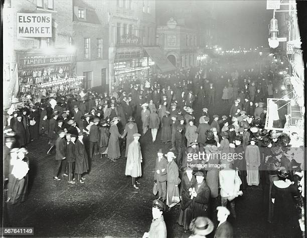 Crowds in Deptford High Street shopping after dark London 1913 Shop fronts including Elston's Market can be seen